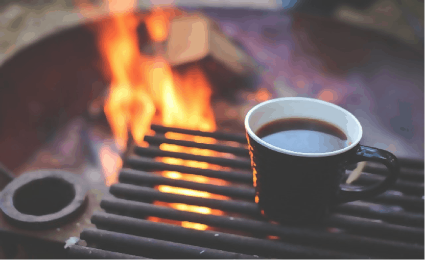Cup of coffee on iron grill plate hovering over a campfire