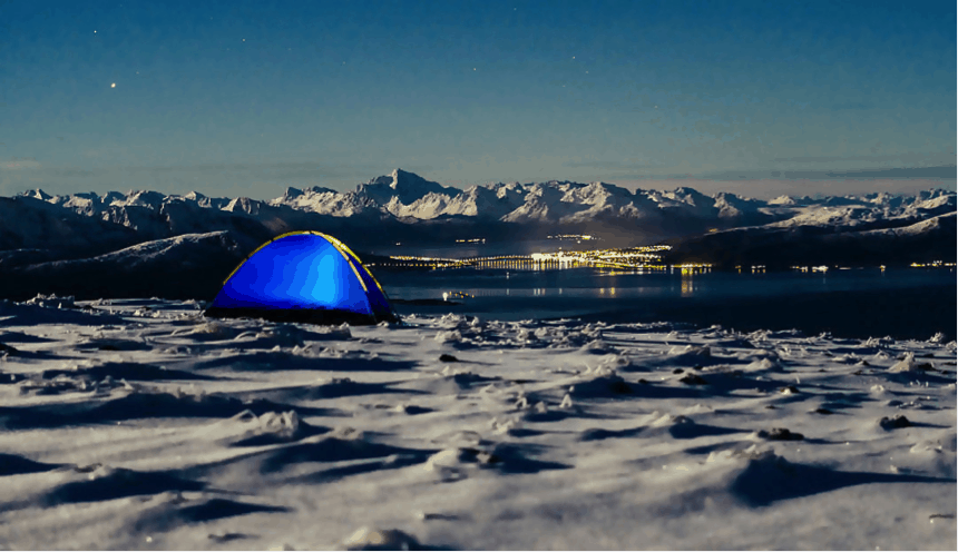Tent on icy ground with lake and small town with mountains in background