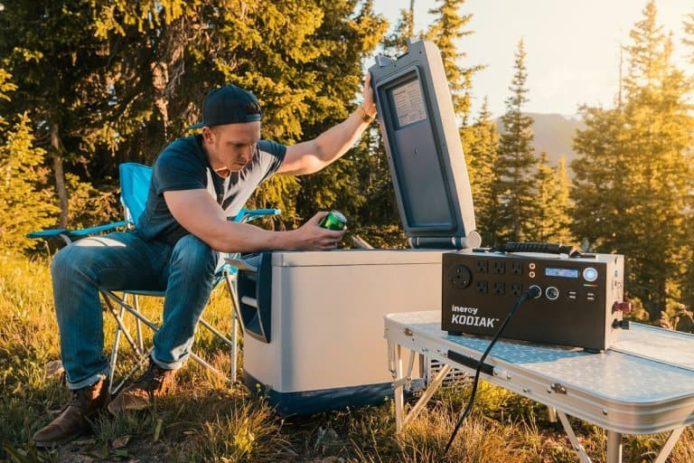 Man grabbing drink out of cooler powered by the Inergy Kodiak solar generator