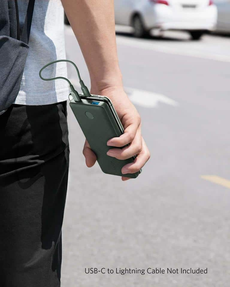 Person carrying phone with battery across street