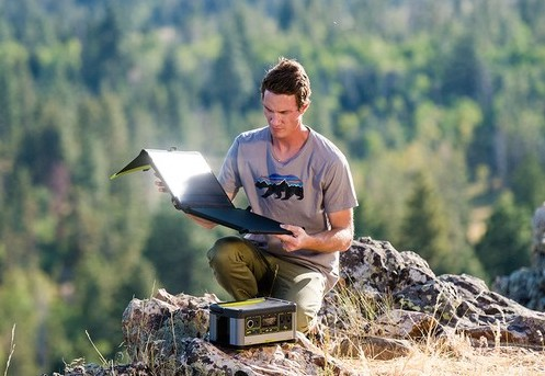 Man on mountain with Nomad 50 solar panel