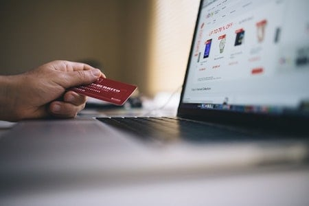 Person holding credit card in front of computer