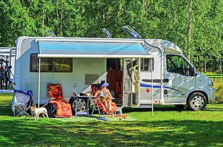 RV parked in grass with woman reading book